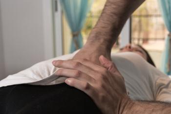 Una mano masajeando sin dolor a una paciente