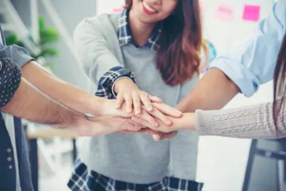 Un equipo dándose la mano, hanciendo piña